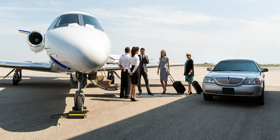 Business people useing Columbus Airport limo service are greeted by flight crew near private jet